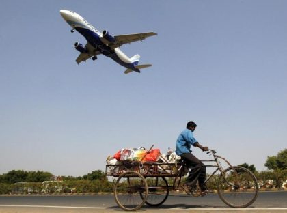 An IndiGo Airlines aircraft prepares to land as a man paddles his cycle rickshaw in Ahmedabad, India, October 26, 2015.  REUTERS/Amit Dave/Files